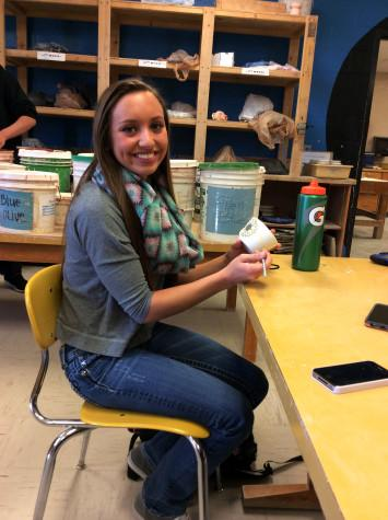 Senior Haley Meier smiles as she adds the finishing touches to the tea cup.