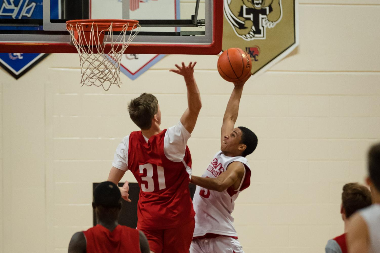 Senior Drew Buchanan soars high and goes for the block on junior Isiah Johnson. They kicked off the night with scripted acts and singing. The boys basketball team scrimmaged for 20 minutes. and were split up into red and white teams.
